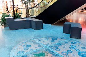 PALA Betonikalusteet penkkejä sinisellä, kuvioidulla lattialla.