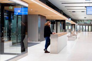 Nainen seisomassa PALA Betonikalusteet pöytätason äärellä Espoon Tapiolan bussiterminaalissa.